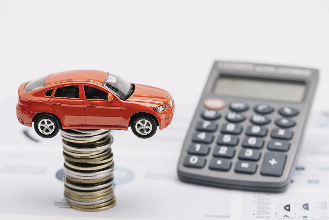 Pilha de moedas com miniatura de carro equilibrada e calculadora sobre planilha de cálculos