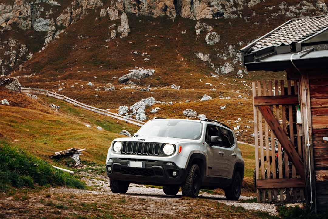 Jeep Renegade prata subindo ladeira em estrada de zona rural