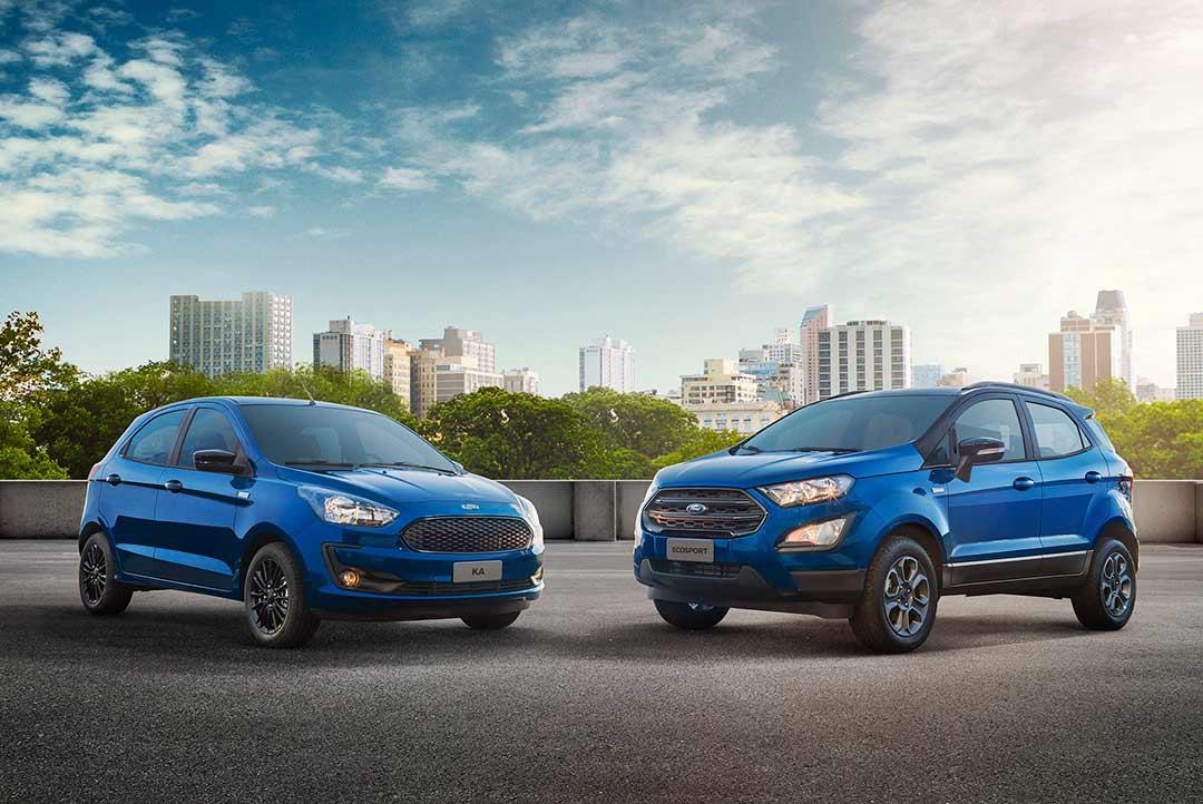 Ford Ka e Ford Ecosport azuis estacionados com prédios da cidade ao fundo