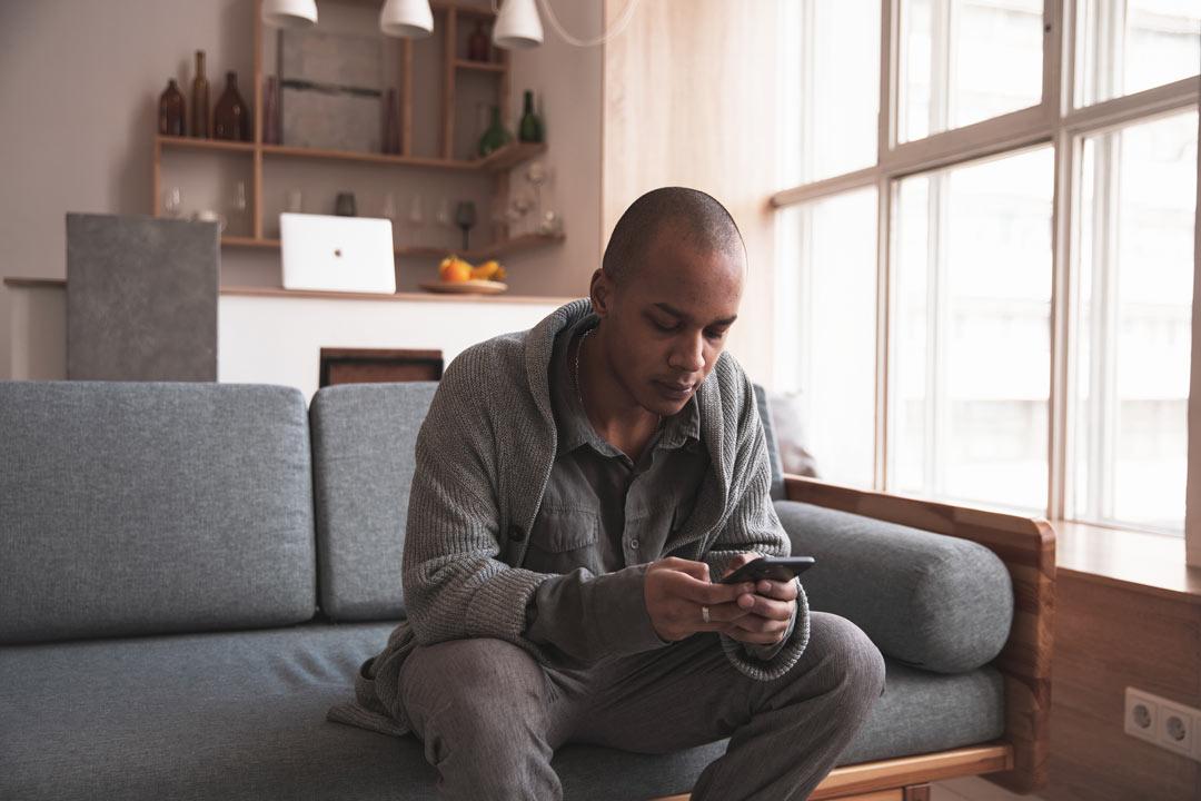 Homem no sofá de sua casa usando aplicativo da CARUPI em seu celular