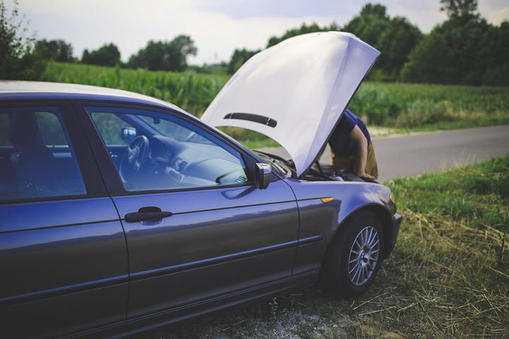 Carro parado à beira da estrada com capô aberto e homem consertando