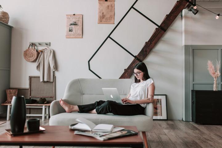 Mulher sentada em sofá digitando em notebook em ambiente moderno e casual