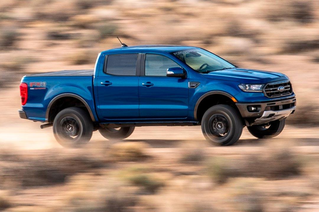 Picape Ford Ranger acelerando em estrada de terra e levantando poeira