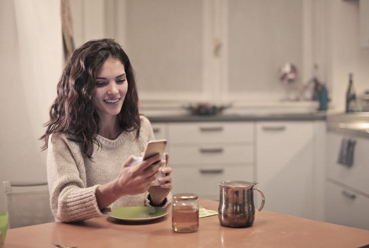 Mulher sentada à mesa da cozinha acessando o aplicativo da CARUPI