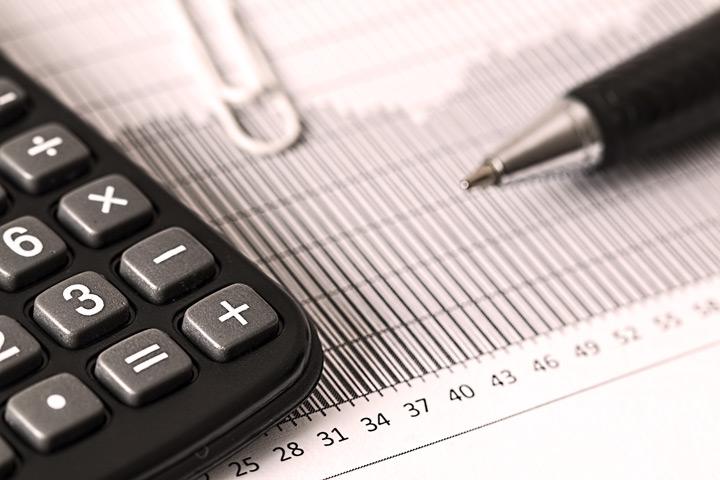 Close up em calculadora e caneta sobre papel com planilha de custos
