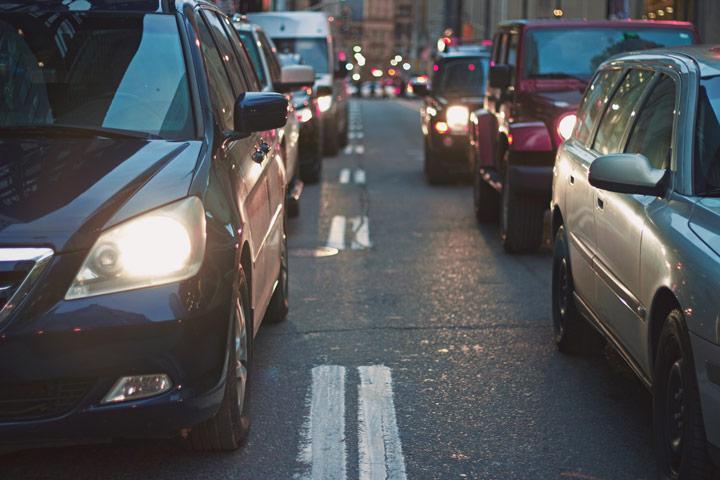 Filas de carros parados em rua congestionada de uma cidade ao anoitecer