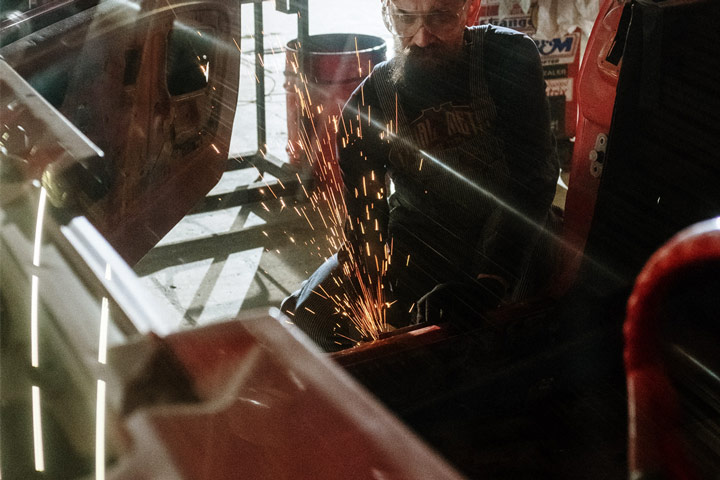 Mecânico usando serra para executar serviço em lataria de um carro