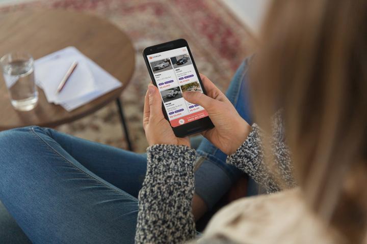 Mulher sentada em sofá de casa acessando website CARUPI em seu celular