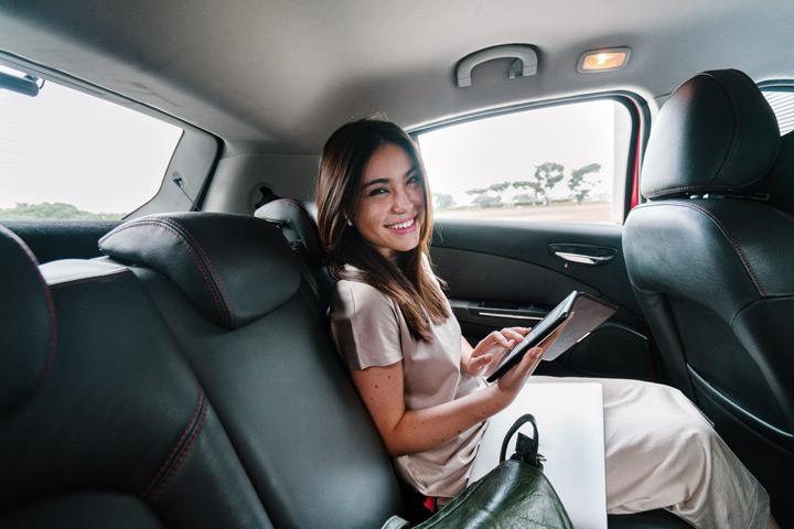 Mulher de negócios sorrindo em banco traseiro de carro enquanto usa um tablet