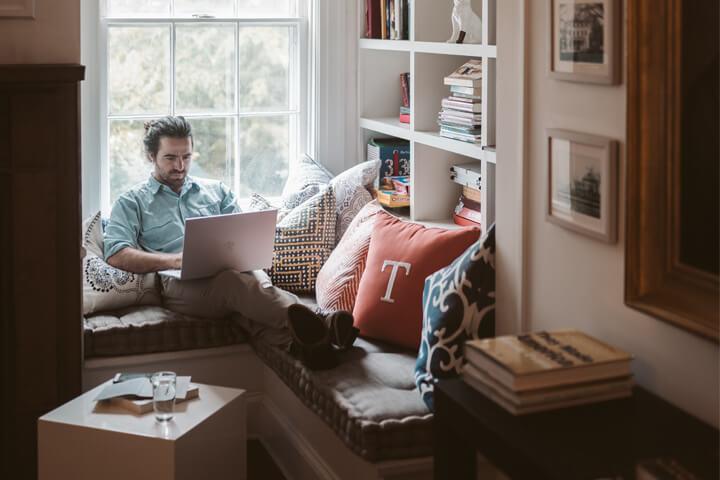 Homem jovem sentado relaxadamente ao lado de janela de sua casa acessando website Carupi no notebook