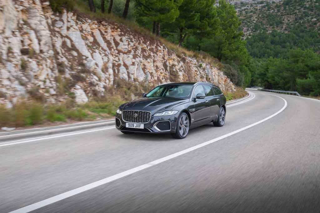 Carro Jaguar XF em rodovia da Europa cercada por pinheiros