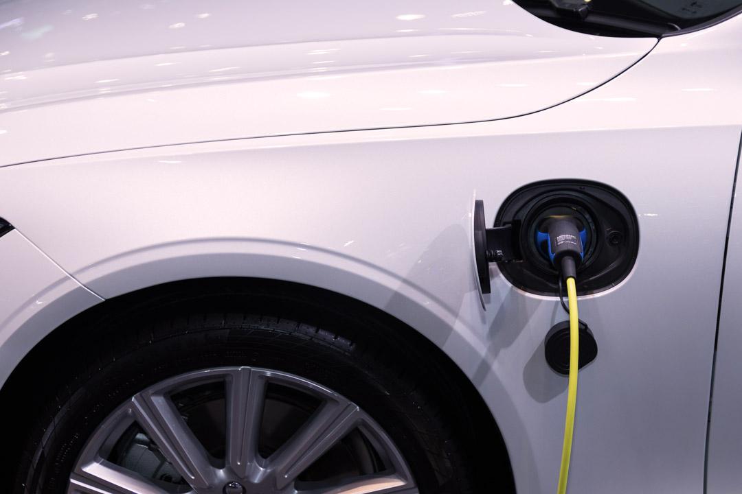 Close em carro elétrico branco com cabo de energia plugado em tomada de carga