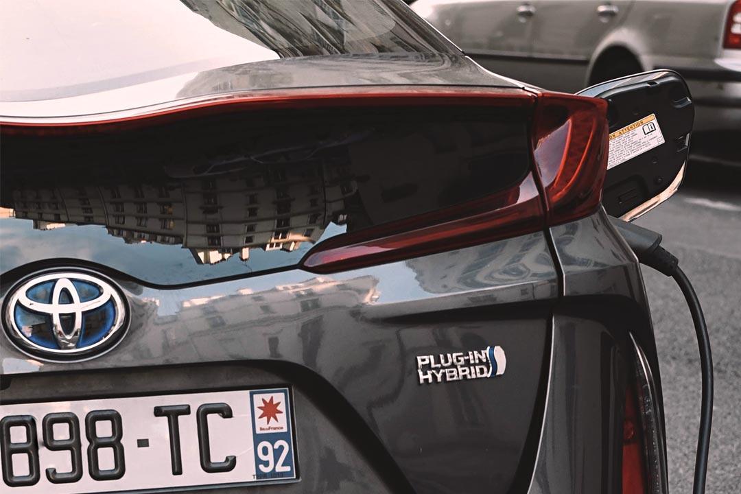 Close em traseira de carro Toyota Prius com cabo de recarga plugado em entrada