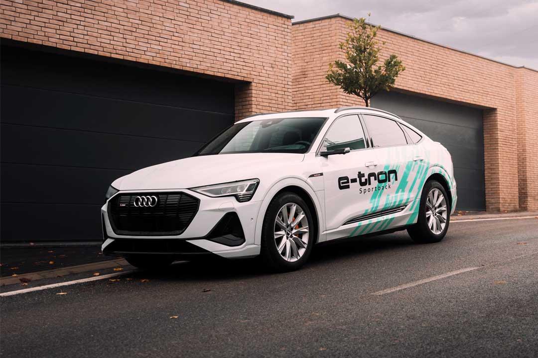 Carro elétrico Audi e-tron estacionado em rua em frente a galpão com portões fechados