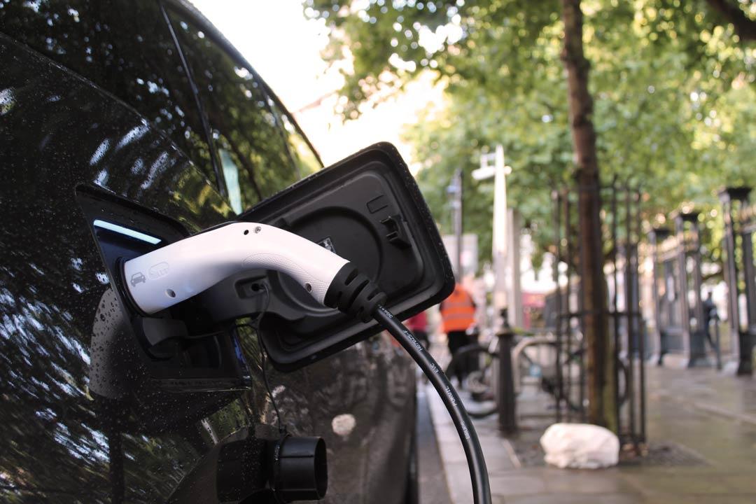 Close de lateral de carro elétrico estacionado em rua recarregando bateria em eletroposto