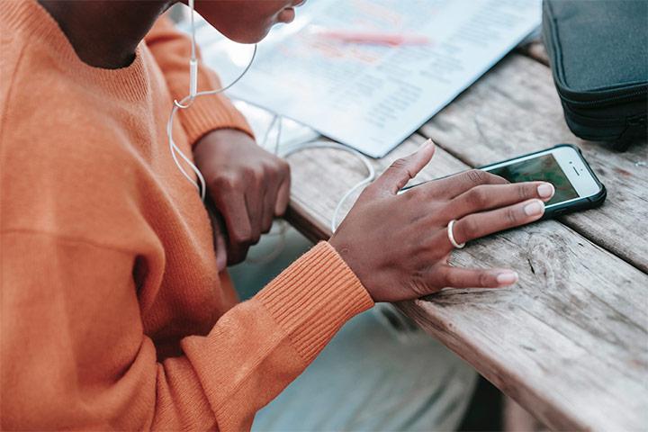 Mulher sentada à mesa mexendo em seu smartphone e ouvindo música com fone de ouvido