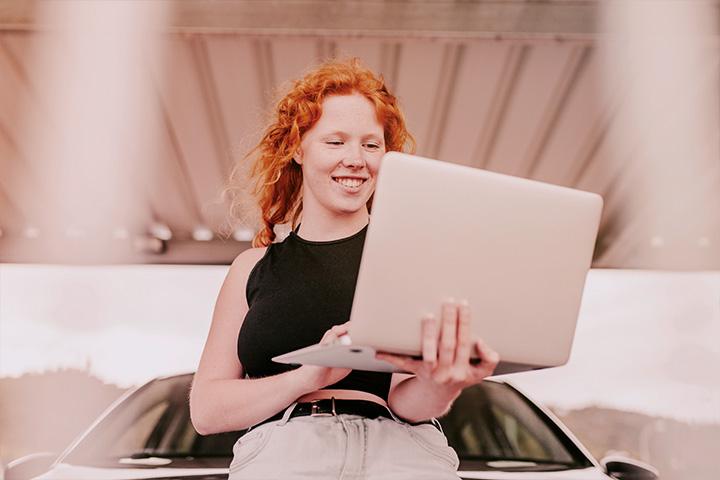Jovem garota de cabelos ruivos apoiada em capô de carro usando computador laptop e sorrindo