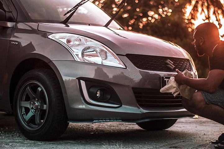 Homem passando pano de limpeza em seu carro ao entardecer