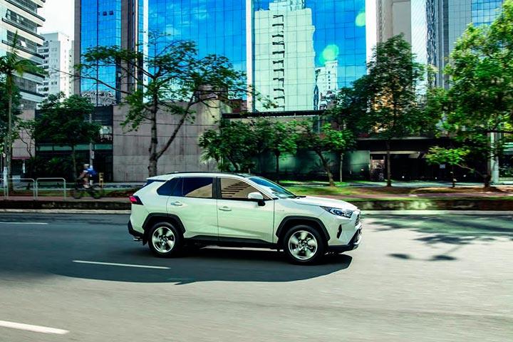 SUV Toyota RAV 4 trafegando por avenida da cidade cercada de prédios espelhados