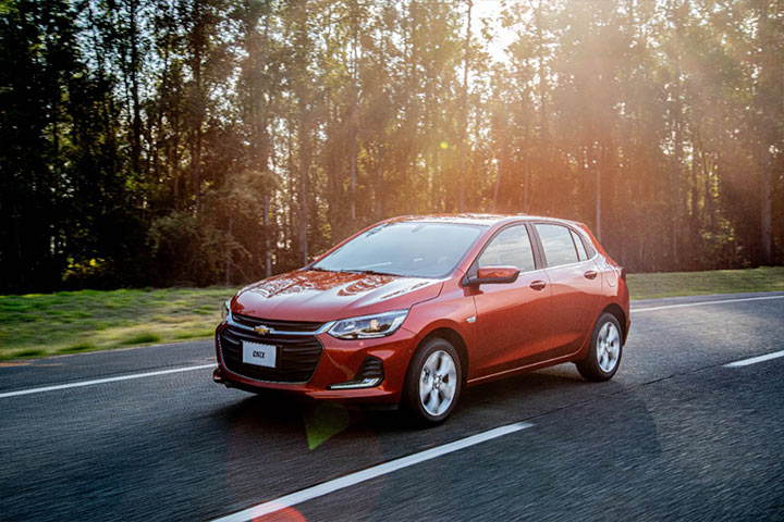 Chevrolet Onix circulando por rodovia arborizada durante entardecer