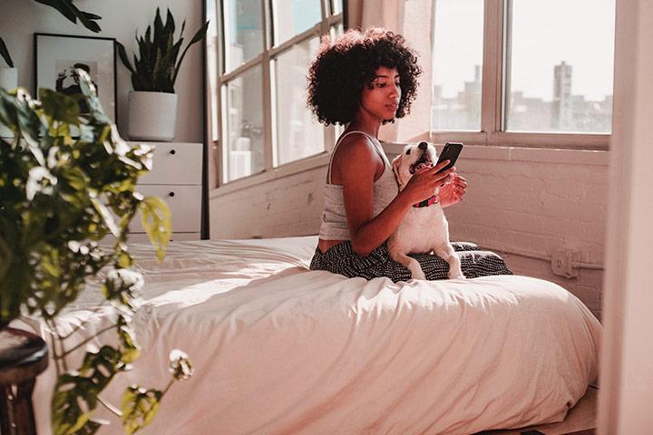 Mulher jovem sentada em cama em frente  janela com cachorro no colo e olhando celular