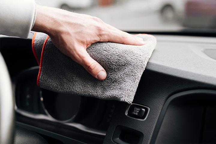 Close de homem limpando painel do carro com uma flanela macia