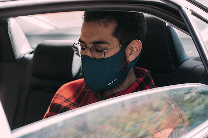 Homem com máscara em banco traseiro de carro de aplicativo de transporte