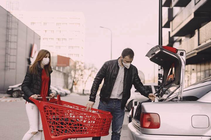Casal guardando compras de mercado em porta-malas de carro
