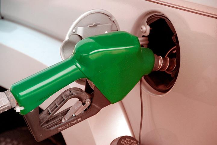 Destaque de bico de mangueira de combustível abastecendo tanque de carro