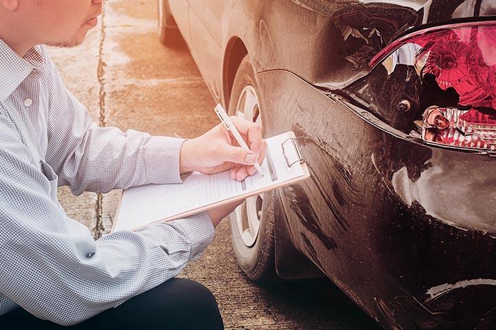 Homem com prancheta checando traseira de carro de perto durante vistoria veicular