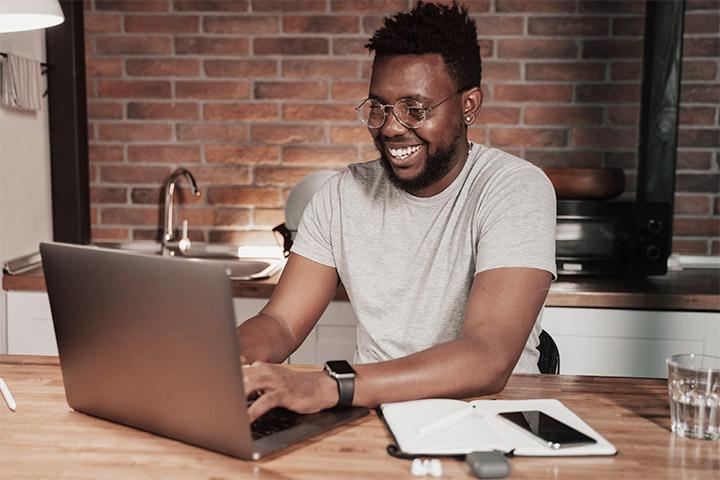 Rapaz sorridente usando laptop em sua casa e  comprando carros online na CARUPI