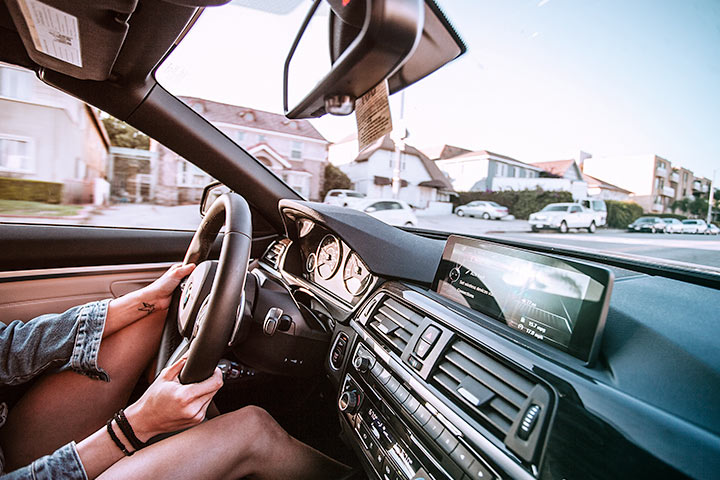 Interior de carro trafegando na rua mostrando mãos no volante e painel do veículo