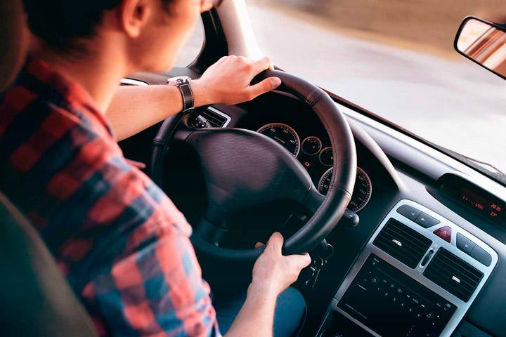 Rapaz dirigindo carro com mãos no volante visto do banco traseiro