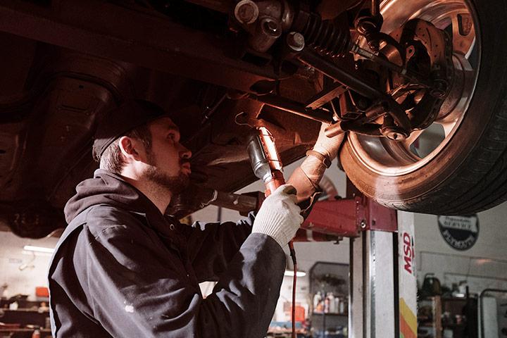 Mecânico usando lanterna para averiguar sistema de direção e rodas de veículo suspenso em oficina