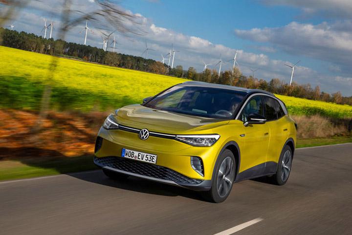 Volkswagen ID.4 amarelo trafegando em rodovia rural com geradores de energia eólica ao fundo