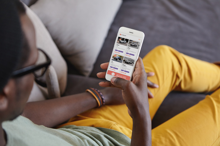 Homem em sofá relaxando e acessando app da CARUPI para escolher seu carro