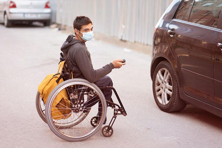 Jovem com deficiência em cadeira de rodas destravando carro adaptado estacionado na rua