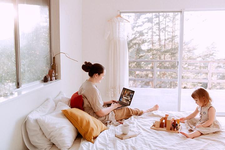 Mãe acessando site da CARUPI em seu laptop sentada em cama de quarto iluminado pela manhã m companhia de filha bebê brincando com bloquinhos