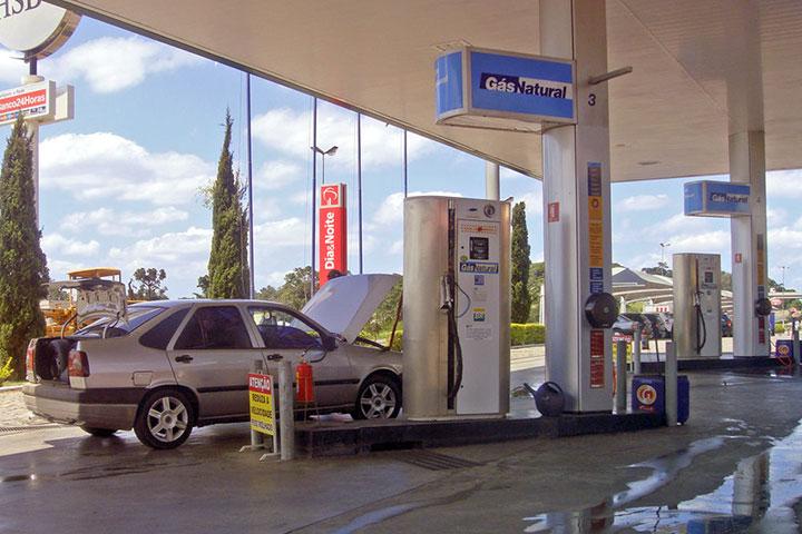 Carro estacionado em posto de abastecimento GNV com capô e porta-malas abertos