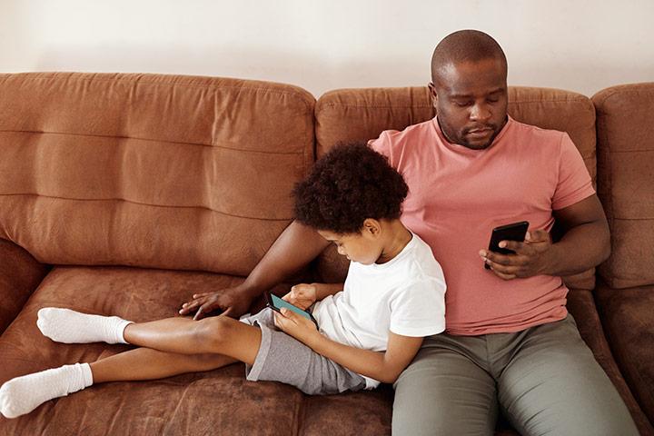 Pai e filho sentados em sofá relaxando e usando smartphones
