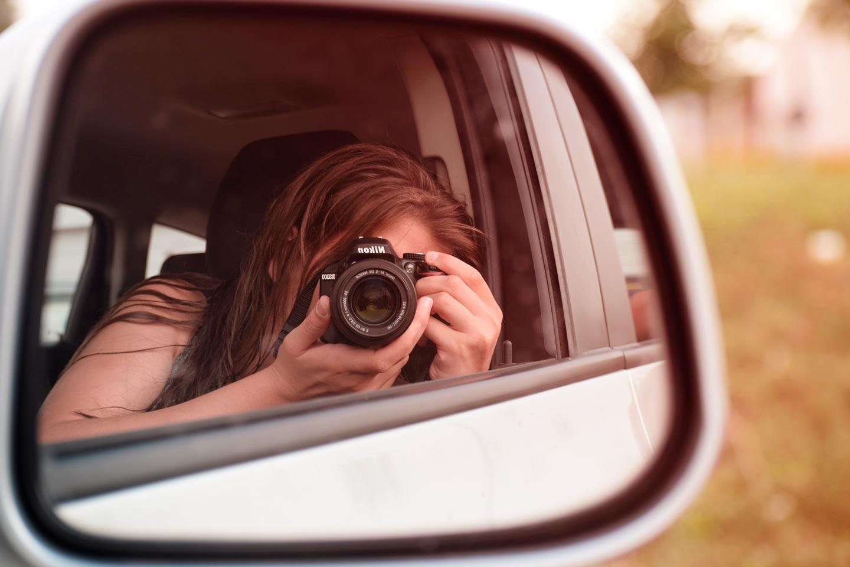 Mulher dentro de carro com câmera fotográfica fotografando retrovisor do veículo que reflete sua imagem