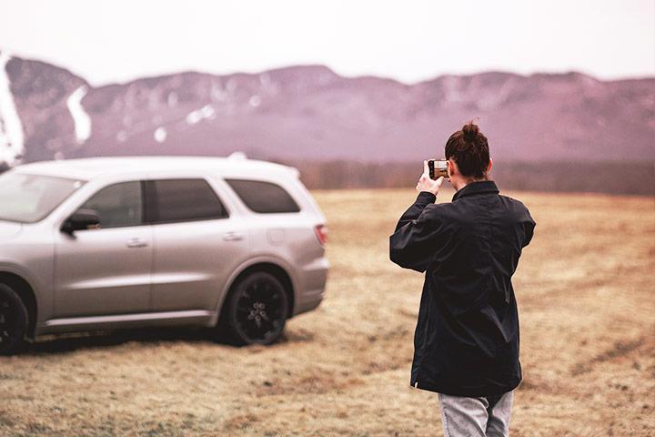 Mulher em ambiente externo fotografando carro com celular em dia nublado com montanhas ao fundo