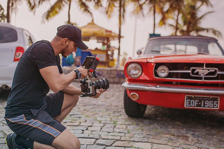 Rapaz fotografando Ford Mustang vermelho em calçada à beira-mar