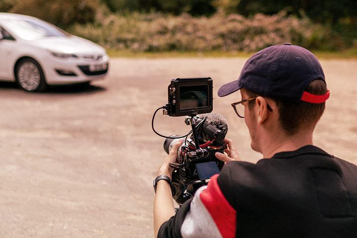 Rapaz agachado com tripé e câmera fotográfica fazendo fotos de carro ao fundo