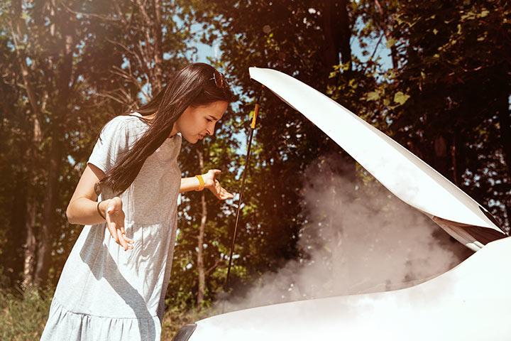 Jovem mulher em dúvida em frente a carro quebrado com capô aberto exalando fumaça