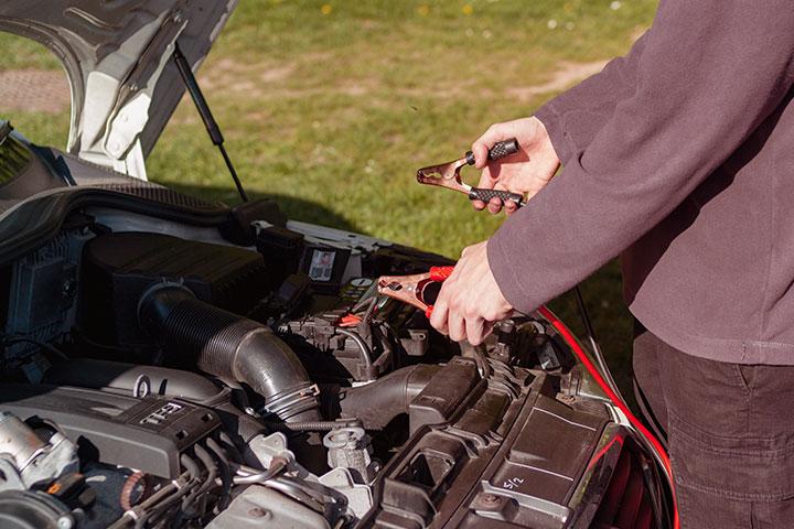 Destaque para homem segurando cabo de chupeta para ligação de bateria de carro com capô aberto