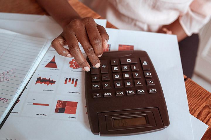 Destaque em mãos de mulher negra usando calculadora em mesa com papéis e cadernos onde faz contas