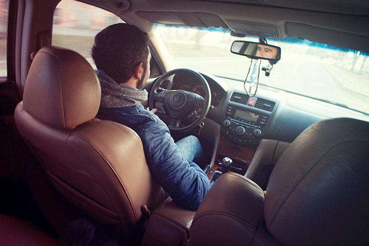Vista traseira de um homem dirigindo carro e fazendo test drive