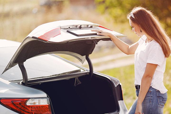Jovem mulher abrindo porta-malas de carro para averiguar seu tamanho interno