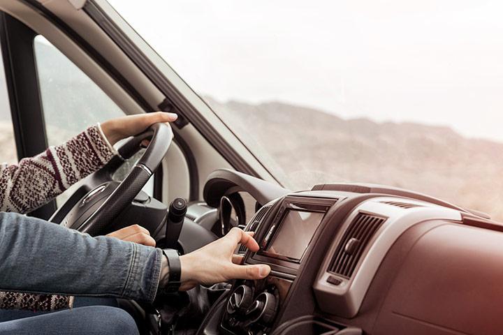 Close de painel de carro com mãos de mulher dirigindo o volante e mão de homem operando central multimídia
